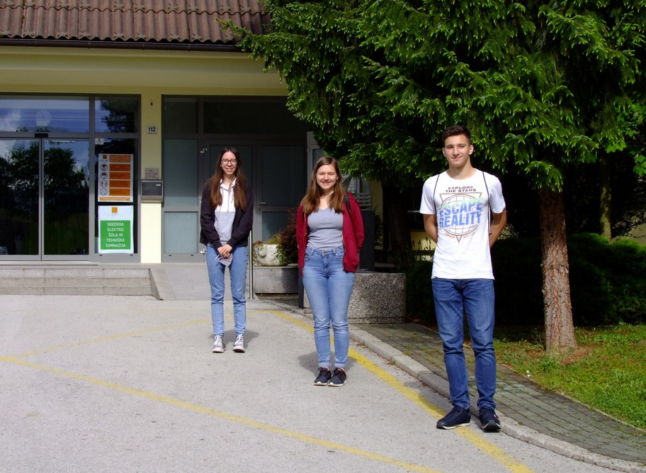 Ema Prevalšek, 4. aG, Marija Absec, 4. aG, in Gal Stopar, 1. aG, pred pričetkom tekmovanja ob vhodu v Šolski center Novo mesto. Foto: Tilen Šetina, prof.